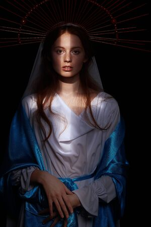 The Virgin Mary portrait on a dark background with rays of light. Modern art in religion. Sacrament of baptism.