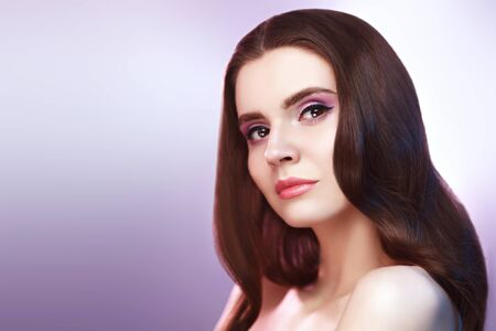 Beauty woman. Portrait of a beautiful young woman with light lilac and purple makeup and long hair. Healthcare, spa and bodycare. Make-up and cosmetics.