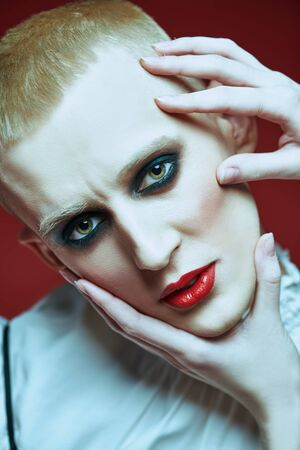 Portrait of a young man with women's makeup with hands touching his face on a red background. Avant-garde fashion.