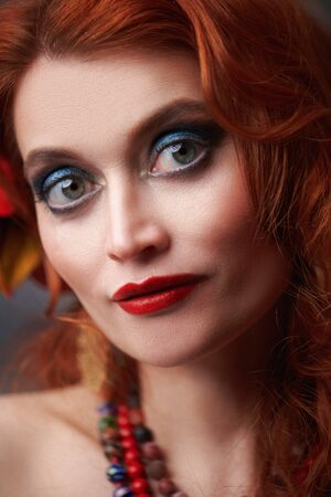 Close up portrait of a beautiful red-haired gypsy woman. National gypsy costume, ethnic. Make-up and hairstyle.
