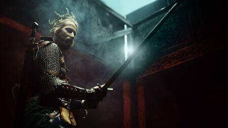Caballero medieval de fantasía con armadura y corona está luchando con una espada en sus manos. El hombre brujo.