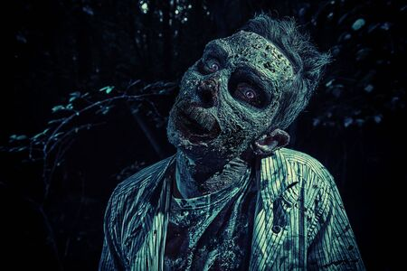Portrait of a horrible bloody zombie in the night forest. Halloween. Thriller.