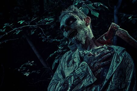 Terrible bloody zombie with an axe around his neck in the night forest. Halloween. Thriller.