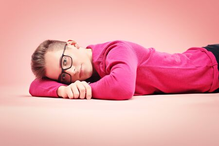 Youth fashion. Happy young guy in modern clothes is posing on a pink background. Holidays and vacations.