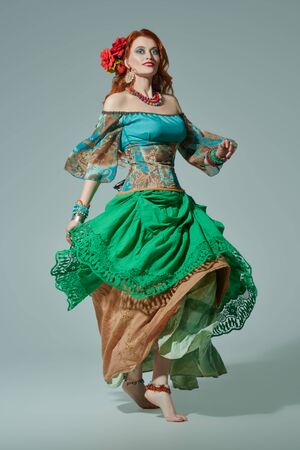 Beautiful red-haired gypsy woman is dancing at studio. National gypsy costume, ethnic. Make-up and hairstyle.