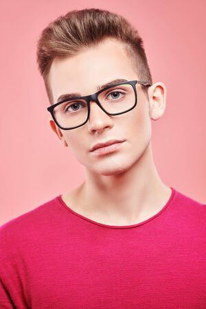 Youth fashion. Elegant young man in modern clothes and glasses posing on a pink background.