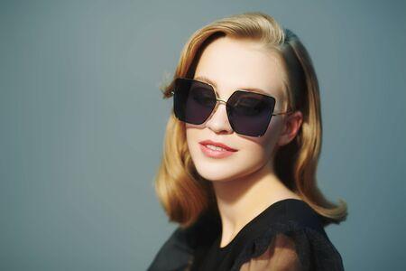 Studio portrait of a beauty fashion blonde model girl wearing stylish glasses. Optics style, eyewear.