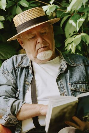 Portrait of an thoughtful elderly man sitting on a bench in the garden reading a book. Summer vacation in the country. Leisure in the park. Stockfoto