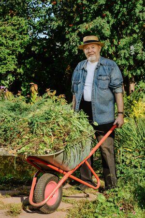 Portrait of an elderly gardener carrying weeds from the garden in a cart.