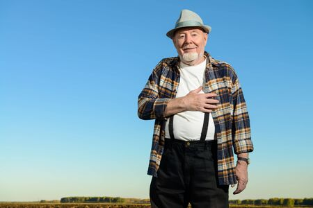 Portrait of an happy elderly man in the field. Summer vacation in the country.