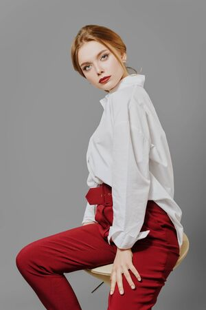 Beauty, fashion portrait. Elegant business style. Portrait of a beautiful blonde woman in white blouse and red pants posing at studio on a gray background.