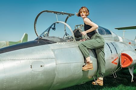 Portrait of a beautiful girl pilot repairing her fighter airplane at the airfield. Imagens
