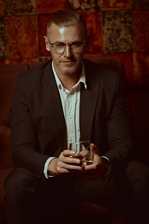 Portrait of a respectable middle-aged man in an expensive suit and glasses drinking whiskey in a luxurious apartment. Success and rich lifestyle.