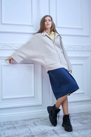 Full length portrait of a pretty blonde girl in a light coat and long skirt posing in a white classic interior. Spring and autumn clothes fashion.