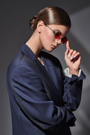 Fashion shot. Portrait of a stylish girl model posing in black man's jacket and round red sunglasses on a gray background with shadows.