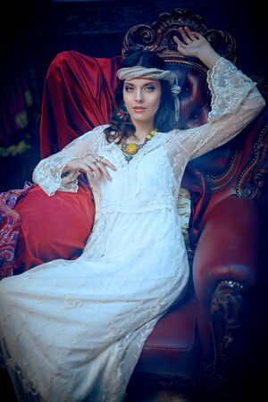 Bohemian lifestyle. Beautiful young woman in elegant lace dress and jewelry posing in a vintage armchair in a luxurious interior. Fashion shot, oriental style. Фото со стока