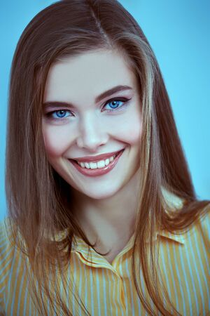 Portrait of a happy beautiful young girl with natural make-up smiling at camera. Studio beauty portrait.