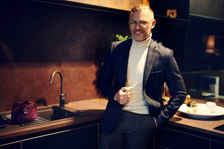 Handsome middle-aged businessman in elegant suit and glasses stands at home on a kitchen and smiles. Working at home. 스톡 콘텐츠
