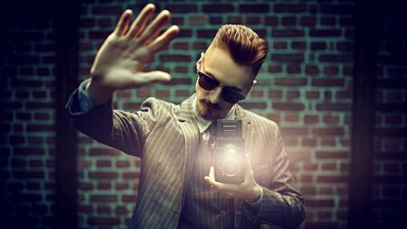 Retro concept. Handsome photographer man in an elegant suit is working with his old camera on a brick wall background. 版權商用圖片