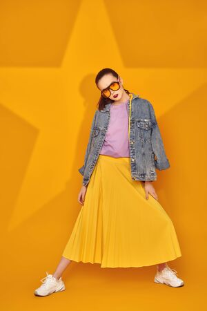 Modern youth look. Beautiful young girl in bright summer clothes posing on a yellow background with a star. Beauty, fashion.