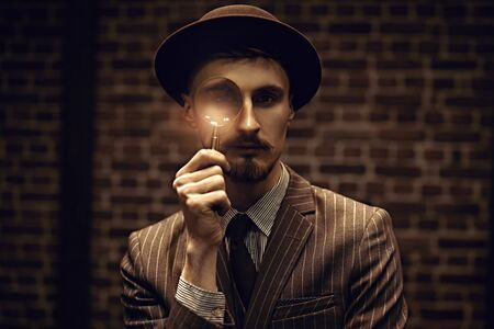 Detective man looking intently through a magnifying glass. Retro style. Occupation, criminal world.