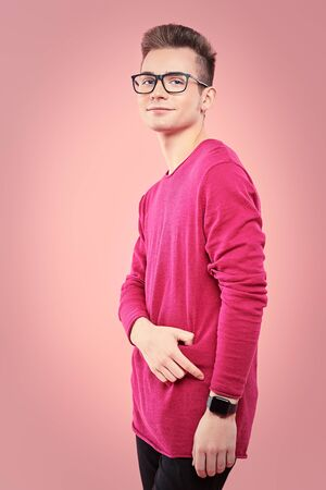 Youth fashion. Happy young guy in modern clothes is posing on a pink background. Study, education.