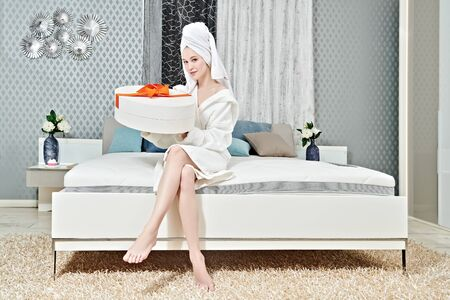 Elegant young woman in a white bathrobe and a towel around her hair after a shower sat down in her cozy bedroom and holds a box with a gift. Home interior, furniture. Lifestyle. Imagens