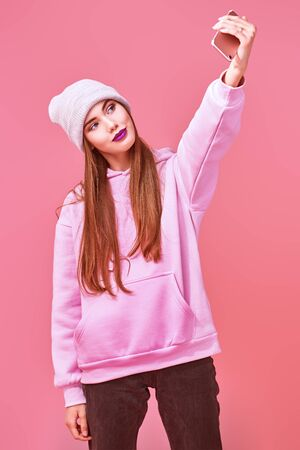 Youth generation. Modern teen girl in a pink sweatshirt and a hat making selfie on her smartphone on a pink background. Social networks concept. Standard-Bild - 147789862