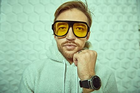 Portrait of a cool young man in white hoody and stylish yellow sunglasses. Youth style, men's fashion.
