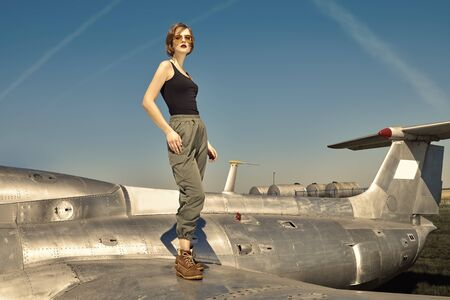 Beautiful girl pilot stands on the wing of a fighter airplane at the airfield. Imagens