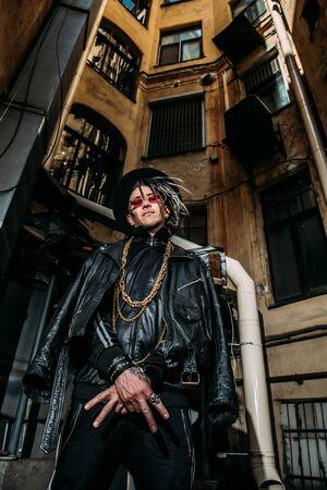 A portrait of a stylish punk man in the street. Modern men fashion.