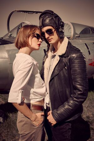 Handsome man pilot stands next to his beautiful girlfriend before the flight. Aviation and love. Retro style. 免版税图像