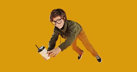 Funny emotional boy teenager in glasses flies with a cup of coffee. Yellow background. Copy space.