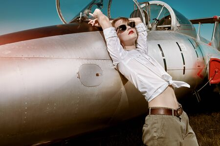 Portrait of a sexual pilot girl standing next to her fighter plane at the airfield.