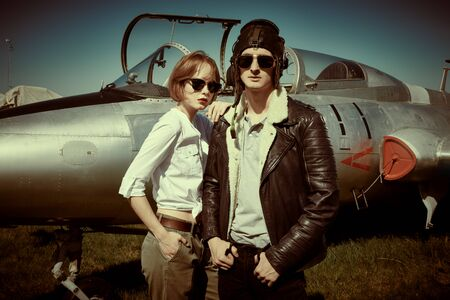 A beautiful girl and a handsome man pilots stand next to a fighter jet at the airfield. Military aircraft. Military fashion. Retro style. 免版税图像