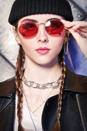 Youth fashion. Trendy young girl with bright make-up wears black leather jacket, black hat and red sunglasses on a grunge background. Urban rock style.