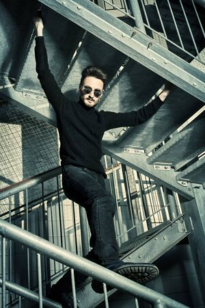 Portrait of a handsome courageous man in black clothes and black sunglasses posing on a metal industrial staircase. Urban grunge style. Male fashion.