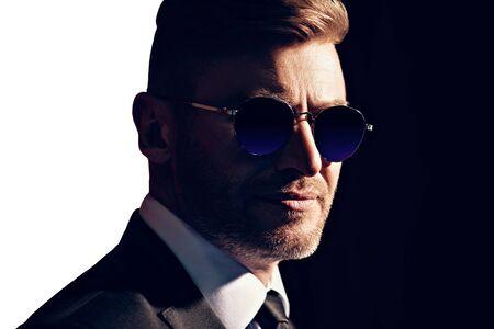 A close up portrait of a brutal handsome man in sunglasses. Men's beauty, fashion. Optics for men.