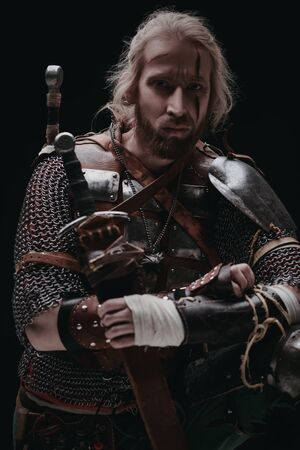 Portrait of a brave medieval warrior in armor with a sword on a black background. The Witcher man.