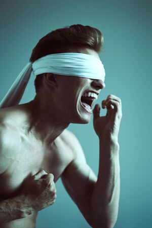 Art portrait of a handsome shouting blindfold man with perfect muscular body, expressing suffering. Copy space. Banque d'images