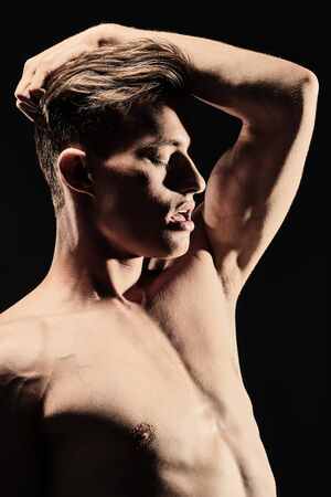 Portrait of a handsome sexual athletic muscular man on a black background. Man's beauty and health. Sports concept.