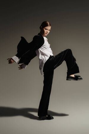 Fashion concept. Full length portrait of a gorgeous graceful young woman model posing in motion in black velvet suit and white shirt on a gray background.