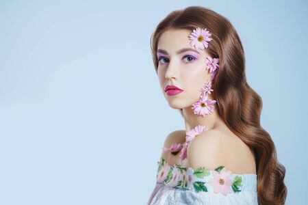Portrait of a beautiful brunette girl with soft lilac flowers of chrysanthemums on her face and body on a white background. Beauty, spa and cosmetics concept. Copy space. Banque d'images - 149582088