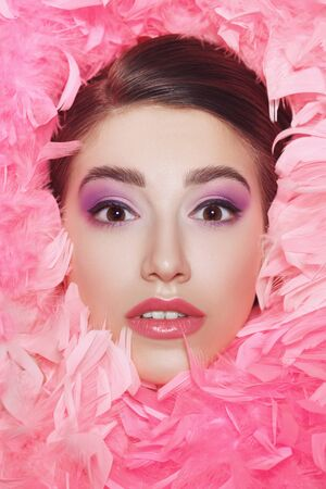 Portrait of a charming young woman with bright purple lilac make-up and fluffy pink boa. Female beauty and fashion concept. Make-up and cosmetics. Banque d'images - 149582090