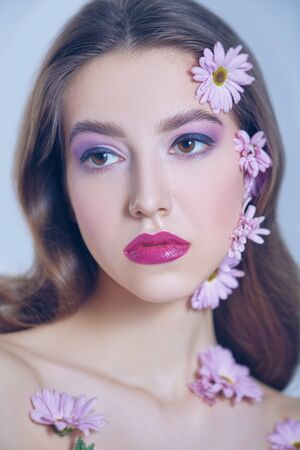 Portrait of a beautiful brunette girl with soft lilac flowers of chrysanthemums on her face and body on a white background. Beauty, spa and cosmetics concept.