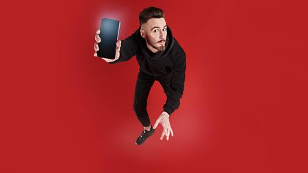 Funny emotional young man is flying through the air with his smartphone. Active lifestyle. Studio portrait on a red background. Copy space. Stok Fotoğraf