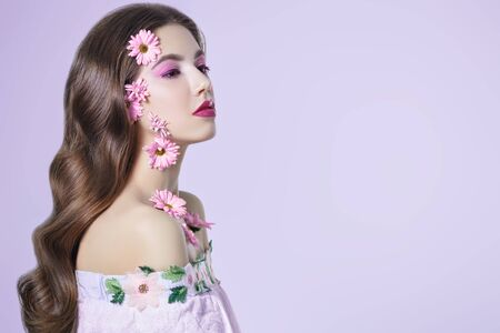 Portrait of a beautiful brunette girl with soft lilac flowers of chrysanthemums on her face and body on a white background. Beauty, spa and cosmetics concept. Copy space. Banque d'images - 149582107