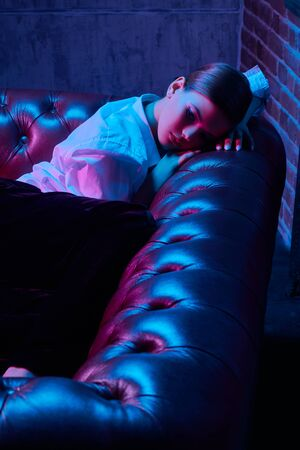 Portrait of a gorgeous young woman in white shirt posing on a leather sofa in colorful bright neon lights. Luxurious lifestyle. Make-up and beauty trends. Banque d'images - 149582112