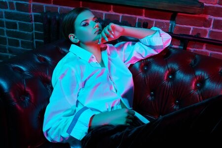 Portrait of a gorgeous young woman in white shirt posing on a leather sofa in colorful bright neon lights. Luxurious lifestyle. Make-up and beauty trends. Banque d'images - 149582123