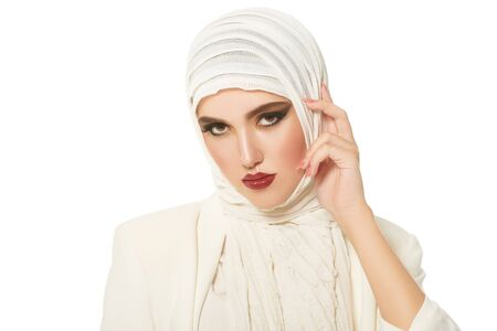 Portrait of a modern muslim woman in fashionable white clothes and white hijab posing on a white background. Oriental beauty, fashion. Make-up and cosmetics.